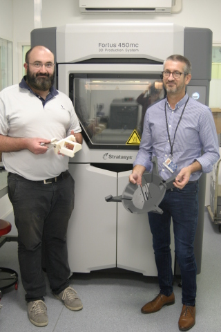 Frédéric Tremoulet, 3D Printer Manager and Mathieu Dumora, UPSA Project Manager, holding 3D printed production tools for the camera mounts (Photo: Business Wire)