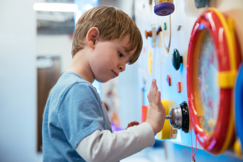 A child explores an activity panel at the Vivint Smart Home Arena sensory room. (Photo: Business Wire)
