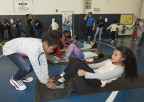 """Nyasia and Xophia, local Hartford Boys & Girls Club members, do sit-ups before rotating to another physical activity during the National Boys & Girls Club Week kick-off event hosted by UnitedHealthcare and Hasbro. UnitedHealthcare donated 100 NERF ENERGY Game Kits to the Boys & Girls Clubs of Hartford's Asylum Hill Unit. This initiative between Hasbro and UnitedHealthcare is designed to encourage kids to increase physical activity. The kits feature Hasbro's NERF products that are designed to encourage young people to become more active through """"exergaming"""" (Photo: Alan Grant / Digital Creations)."""