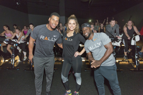 """Due to inclement weather forcing the cancellation of Rally HealthFest planned in Chicago's Maggie Daley Park, Rally Health Ambassadors Kevin Hart and Maria Menounos dropped into Midtown Athletic Club for a pop-up workout. Here, (from right to left) Kevin Hart, Maria Menounos and Kevin's trainer Ron """"Boss"""" Everline surprise spin class participants at a Chicago gym. (Photo: Business Wire)"""