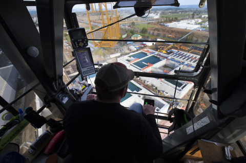 From inside his cab 150 feet above the Hillsboro, Oregon, job site, crane operator Darren Starks looks down on Intel's under-construction water recycling plant. Starks can hoist skyward up to 40 tons at a time, and on a busy day is responsible for about 80 lifts of construction equipment, piping and other gear. When the recycling plant is completed, it will help Intel cut its manufacturing water use. Intel has set a goal to return 100 percent of its water to communities and watersheds for local use by 2025. (Credit: Walden Kirsch/Intel Corporation)