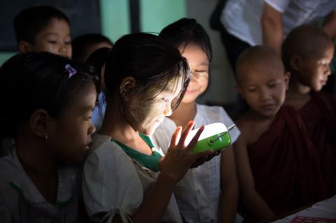 ソーラーランタンの明かりに喜ぶミャンマーの小学校生徒(写真:ビジネスワイヤ)