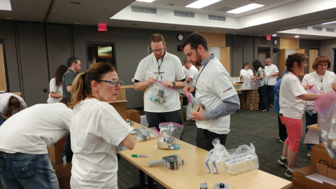 Harris Corporation employees in Rochester, New York, help assemble hygiene kits as part of a company-sponsored service event to support those in need. (Photo: Business Wire)
