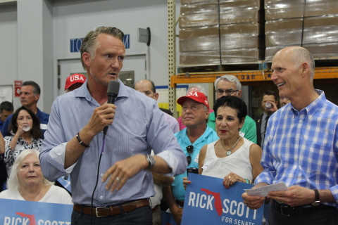 Jeff Jackson standing with Gov. Rick Scott as he addressed the crowd. (Photo: Business Wire)