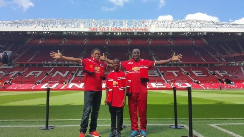 "Taking It All In: ""Here we are at Old Trafford – The Theatre of Dreams"" one of two Flow Skills winners, 12 year Jamaican Brian Burkett (center) is flanked by his coach Mitchily Waul (left) and father, Albert Burkett (right). (Photo: Business Wire)"