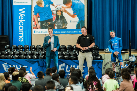 UnitedHealthcare CEO Steve Nelson (left) joins Sacramento Sheriff's Deputy Joe Gordon (center) and UnitedHealthcare Pro Cycling team member Luke Keough (right) to give third-grade students at Howe Avenue Elementary School new helmets and discuss bike safety and healthy lifestyles during a National Bicycle Safety Month event in Sacramento ahead of the final stage of the Amgen Tour of California (Photo: Shannon Rosan).