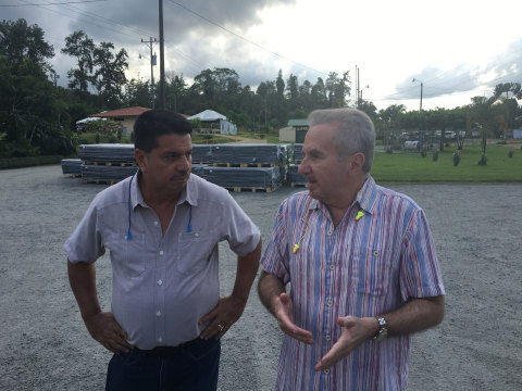 Jose Miguel Ramirez (left), General Manager of Recyplast, leads a tour of Recyplast's manufacturing operation in Siquirres, Costa Rica in an event commemorating the 25th Anniversary of this pioneering enterprise. Renato Acuña, President of Dole Fresh Fruit, comments on ideas for future plant expansion. In the background, plastic recycled corner boards ready for shipment to fresh fruit exporters.