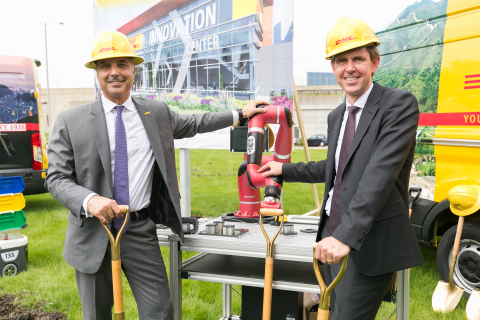 Mike Parra, CEO for DHL Express Americas and Matthias Heutger, SVP, Global Head of Innovation & Commercial Development at DHL, celebrate the groundbreaking of DHL's Americas Innovation Center with Sawyer, a collaborative robot that supports production and DHL warehouse staff by automating repetitive tasks. (Photo: Business Wire)