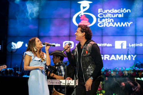Nicolle Horbath, scholarship winner, and Carlos Vives performing together (Photo: Business Wire)