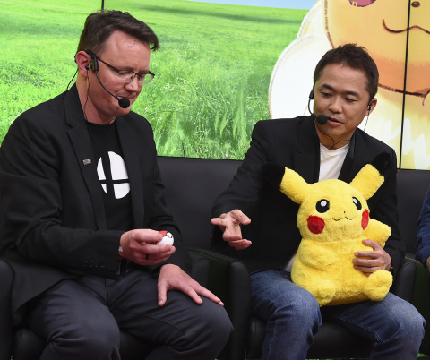 In this photo provided by Nintendo of America, Bill Trinen (left) of Nintendo of America and video game developer Junichi Masuda explain how the Poké Ball Plus accessory can be used to catch Pokémon in the upcoming Pokémon: Let's Go, Pikachu! and Pokémon: Let's Go, Eevee! games for the Nintendo Switch system. Nintendo provided details about the games during the E3 video game trade show in Los Angeles on June 12, 2018. (Photo by Jordan Strauss/Invision for Nintendo/AP Images)