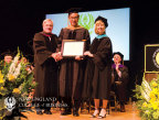"""Former Attorney General and Current Chairman of the NECB Board of Trustees, Scott Harshbarger (left) and NECB Provost, Debra Leahy (right) confer an honorary """"Doctor of Commerce"""" degree on Dr. David Woo (middle). Dr. Woo is one of the world's leading economists and was also the day's keynote speaker, emphasizing to the graduates the power which each of them now wields. (Photo: Business Wire)"""