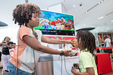 In this photo provided by Nintendo of America, Danielle W. and son Tristan W., age 7, from Queens, NY, celebrate International Sushi Day by enjoying sushi and playing the new Sushi Striker: The Way of Sushido game during a special event at the Nintendo NY store in Rockefeller Plaza. An action-packed puzzle game that's all about matching plates and eating sushi, Sushi Striker: The Way of Sushido is now available for the Nintendo Switch system and in 2D for the Nintendo 3DS family of systems. A free demo is also available in Nintendo eShop on Nintendo Switch – perfect for International Sushi Day on June 18! (Photo: Business Wire)