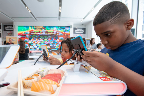 In this photo provided by Nintendo of America, Tristan W, age 7, from Queens, NY, and Isaiah M., age 7, from Queens, NY, celebrate International Sushi Day by playing the new Sushi Striker: The Way of Sushido game during a special event at the Nintendo NY store in Rockefeller Plaza. An action-packed puzzle game that's all about matching plates and eating sushi, Sushi Striker: The Way of Sushido is now available for the Nintendo Switch system and in 2D for the Nintendo 3DS family of systems. A free demo is also available in Nintendo eShop on Nintendo Switch – perfect for International Sushi Day on June 18! (Photo: Business Wire)