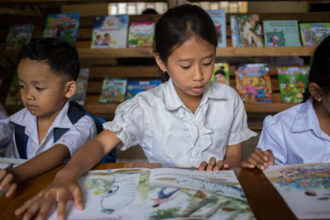 A student reads a local language children's book in the new Room to Read library at Banlech Prasat Primary School, Prey Veng Province, Cambodia. (Photo: Business Wire)