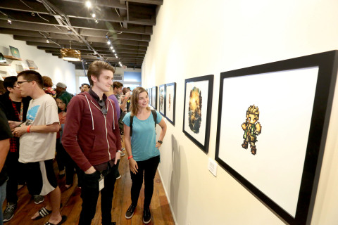 In this photo provided by Nintendo of America, fans look at artwork of Octopath Traveler and enjoy a launch celebration at iam8bit Gallery in Los Angeles. Octopath Traveler is now available in Nintendo eShop on Nintendo Switch and is available at retailers on July 13.