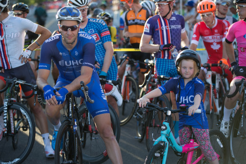 """UnitedHealthcare pro cycling team member Adrian Hegyvary waits with UnitedHealthcare Children's Foundation grant recipient and """"Pro Cyclist for the Day"""" Claire Jensen, 5, at the start of the Twilight Criterium in downtown Boise Saturday, July 14. As """"Pro Cyclist for the Day,"""" Claire participated in the pre-race athlete call-ups and rode in the official pace car at the beginning of the race (Photo: Otto Kitsinger)."""