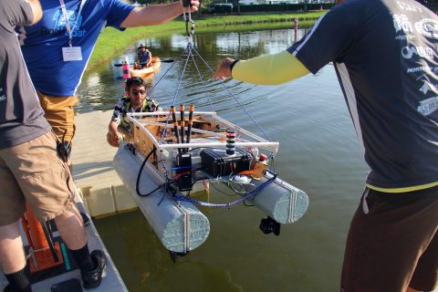 A RoboBoat team gingerly lowers their AV boat into the water. (Photo: Business Wire)