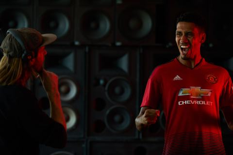 """Manchester United defender, Chris Smalling, celebrates in front of a wall of speakers during a Chivas film shoot in July in Los Angeles, United States. The film was released to announce Chivas as the """"Official Global Spirits Partner"""" of Manchester United. Photographer: Monroe Alvarez"""