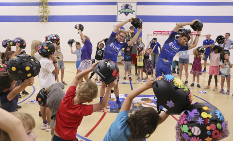 UnitedHealthcare pro cyclists Tanner Putt and Daniel Eaton lead healthy exercises and stretches with kids from the Denver Metro YMCA during a helmet giveaway event ahead of the Colorado Classic pro cycling race next week in downtown Denver (Photo: Barry Gutierrez).