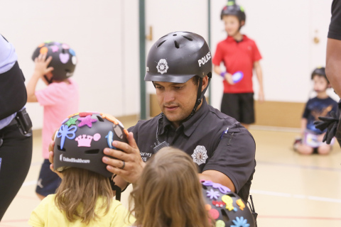 Denver Bike Unit police officer James Harvey helps fit new bike helmets donated by UnitedHealthcare to YMCA youth at a helmet safety event to promote bike safety, exercise and healthy living (Photo: Barry Gutierrez).