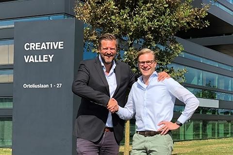 Eldert van Wijngaarden (Web-IQ) and Philip van Waning (FRISS) shaking hands. (Photo: Business Wire)