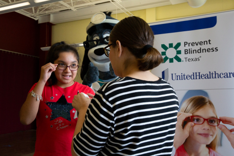 Rubi Camarena is cheered on by Dr. Health E. Hound as she receives a free vision screening from a ce ...
