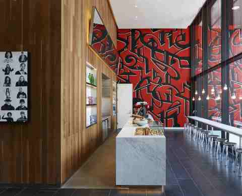 To the right of the check-in/check-out kiosks is coffeeM, citizenM's signature café open to guests and the public. (Photo: Business Wire)