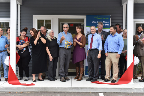 Development partners, community leaders and newly moved-in residents celebrate the opening of Woodland Place Apartments during a ribbon-cutting ceremony (Photo: Nick Azarro).