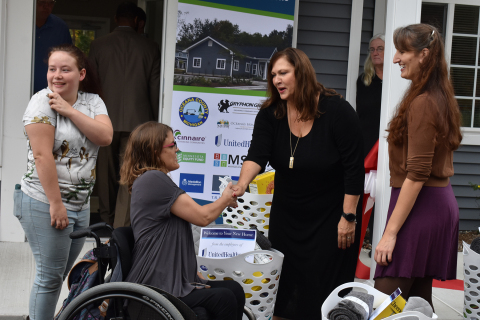 Woodland Place residents Jennifer Syer (center) and Alyssa Whatley (left) receive a welcome basket filled with household items and healthy foods from UnitedHealthcare's Melanie Osment (center right) and Oceana's Home Partnership's Kittie Tuinstra (far right) (Photo: Nick Azarro)