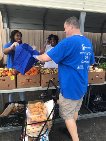 World Finance employees Aricia Grant (left) and Patrick Williams (front) joined community volunteers, including Rhonda Quinn, in New Orleans at a World Food Day 2018 mobile food pantry offered in conjunction with local food pantry Second Harvest Food Bank Feeding South Louisiana. World Finance donated $75,000 on World Food Day to three Feeding America affiliates across the country. (Photo: Business Wire)