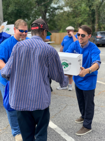 World Finance volunteers Jeff Baker (left) and Dave Dean (right) help distribute food at a mobile food pantry offered through Harvest Hope Food Bank near Greenville, SC. World Finance donated $75,000 on World Food Day, October 16, 2018, and hosted mobile food pantries in conjunction with three Feeding America affiliates across the US. (Photo: Business Wire)