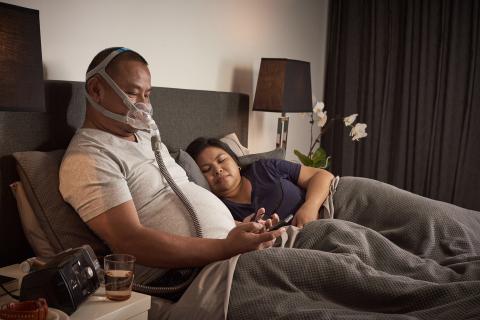 AirFit F30フルフェイスCPAPマスクをベッドで装着している男性 (写真:ビジネスワイヤ)