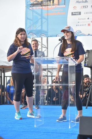Friendship Foundation pals Talia Colen and Gaby Gomez take the stage at the Skechers Pier to Pier Friendship Walk. The annual event has helped launch Friendship Foundation clubs at more than 30 schools across Southern California. (Photo: Business Wire)