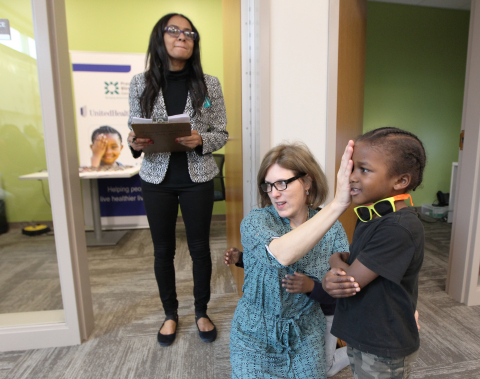 Dr. Rachel Sweeney (C) and DeAndria Nichols (L) of Prevent Blindness Georgia administer a comprehensive eye exam for Torrion (age 4) during a vision screening event for Sheltering Arms students in Atlanta (Photo: Tami Chappell).