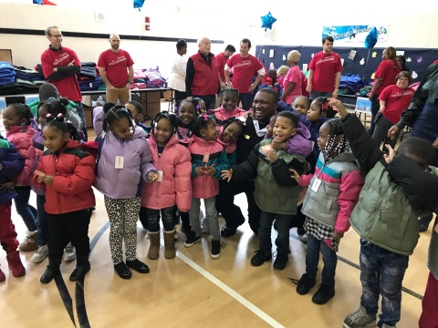 Chicago District 15 Sgt. Jermaine Harris, center, joined Wells Fargo volunteers distributing warm co ...