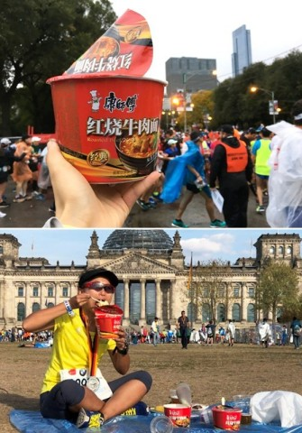 Chinese runner replenishing their energy with instant noodles before starting the Berlin Marathon (P ...