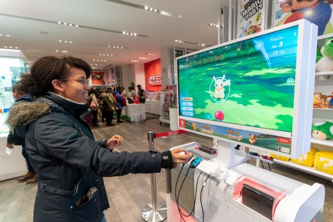 In this photo provided by Nintendo of America, Heather M. of Brooklyn, NY enjoys the immersive Poké Ball Plus accessory that can be used to play the Pokémon: Let's Go, Pikachu! and Pokémon: Let's Go, Eevee! games, now available exclusively for the Nintendo Switch system, at the midnight launch celebration at the Nintendo NY store. The games, along with the Poké Ball Plus accessory, each launched exclusively for the Nintendo Switch system on Nov. 16, 2018. (Photo: Business Wire)