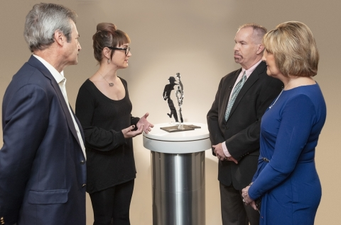 Artist Julie B. explains to Dr. Matthew Stern, Steve and Leslie Peters the meaning of the sculpture and how it reflects Steve's OFF period symptoms, and potentially the symptoms of other people with Parkinson's. (Photo: Business Wire)