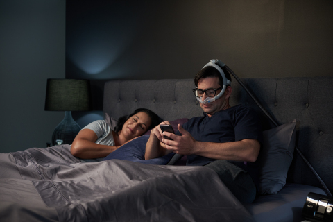 Man reading in bed with AirFit N30i nasal CPAP mask (Photo: Business Wire)