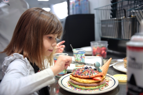 IHOP Kid Chef Nellie Mainor, 8, puts the finishing touches on her PaNellie Unicorn Pancakes. Nellie, who was treated at a Children's Miracle Network Hospital in Salt Lake City, Utah, is one of three finalists for the IHOP Free Pancake Day fundraising campaign, which culminates on Tuesday, March 12. (Photo: Business Wire)