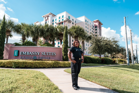 Hilton Team Member Serby Castro stands in front of the Embassy Suites by Hilton property in Orlando where she collects leftover hygiene products to donate to countries in need. (Photo: Hilton)