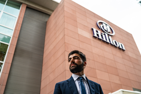 Hilton Team Member Ismaeil Dawod stands in front of the Hilton Frankfurt where he participates in an apprenticeship program that gives him exposure to various hotel departments. (Photo: Hilton)