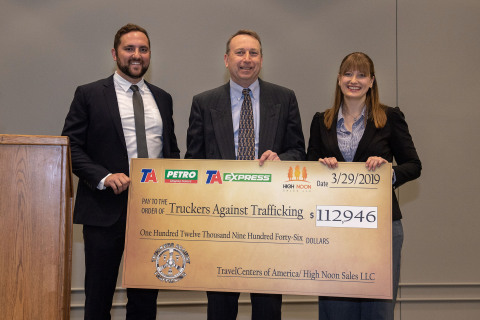 High Noon Productions VP of Sales and Marketing Justin Hoffman and Tom Neubold, SVP Stores for TravelCenters of America, LLC present Helen Van Dam, Freedom Drivers Project Director at Truckers Against Trafficking (TAT) with a check for $112,946 from proceeds raised in January and February through sales of Truckers Against Trafficking merchandise in TA, Petro and TA Express locations. (Photo: Business Wire)