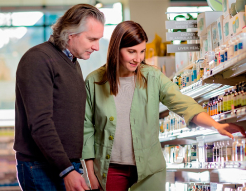 Younger woman helping an older man sort through Functional Remedies hemp oil on a shelf in a pharmacy-like store. (Photo: Business Wire)