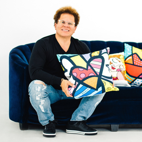 Artist Romero Britto poses with pillows featuring his artwork. The 18-inch square pillows are available exclusively from Lamps Plus. (Photo: Lamps Plus)