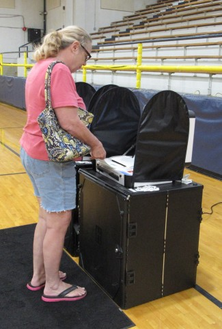 In Hamilton County, a voter scans her hand-marked ballot directly into Verity Scan. The ballot drops ...