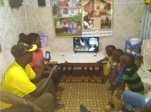 A Kenyan family enjoying the benefits of the Sun King Home 400 with a 24-inch TV (Photo: Business Wire)