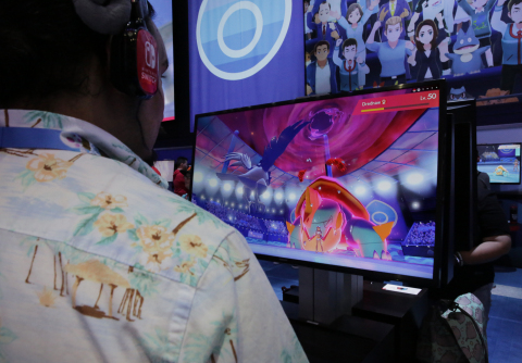 In this photo provided by Nintendo of America, a fan tries out the new larger-than-life Dynamax battle feature while playing Pokémon Sword and Pokémon Shield in the Nintendo booth on June 11, 2019, at the E3 video game conference in Los Angeles, Pokémon Sword and Pokémon Shield launch exclusively for Nintendo Switch on Nov. 15. (Photo: Business Wire)