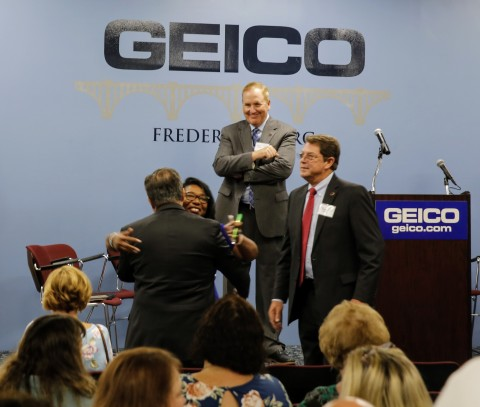 Regional Vice President Scott Markel looks on as two associates reunite at GEICO's 25th anniversary of the Fredericksburg, Va. location. (Photo: Business Wire)