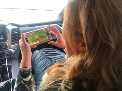 Trisha Yearwood plays FarmVille on her mobile phone while driving to the CMT Awards (Photo: Business Wire)
